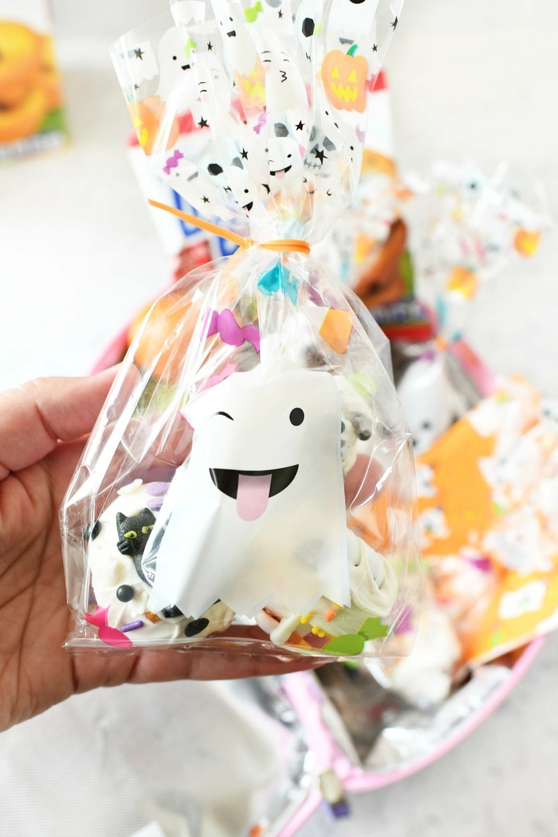 A hand holding a ghost treat bag.