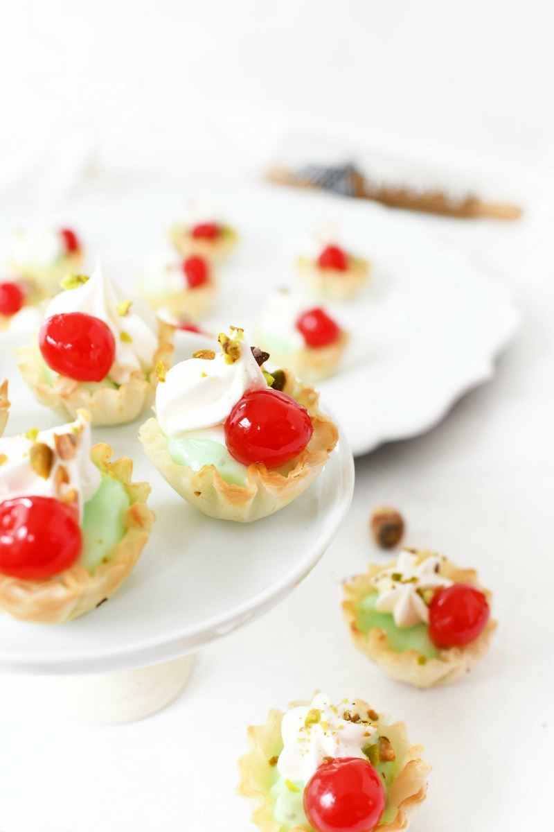 Christmas desserts with cherries on a white platter.