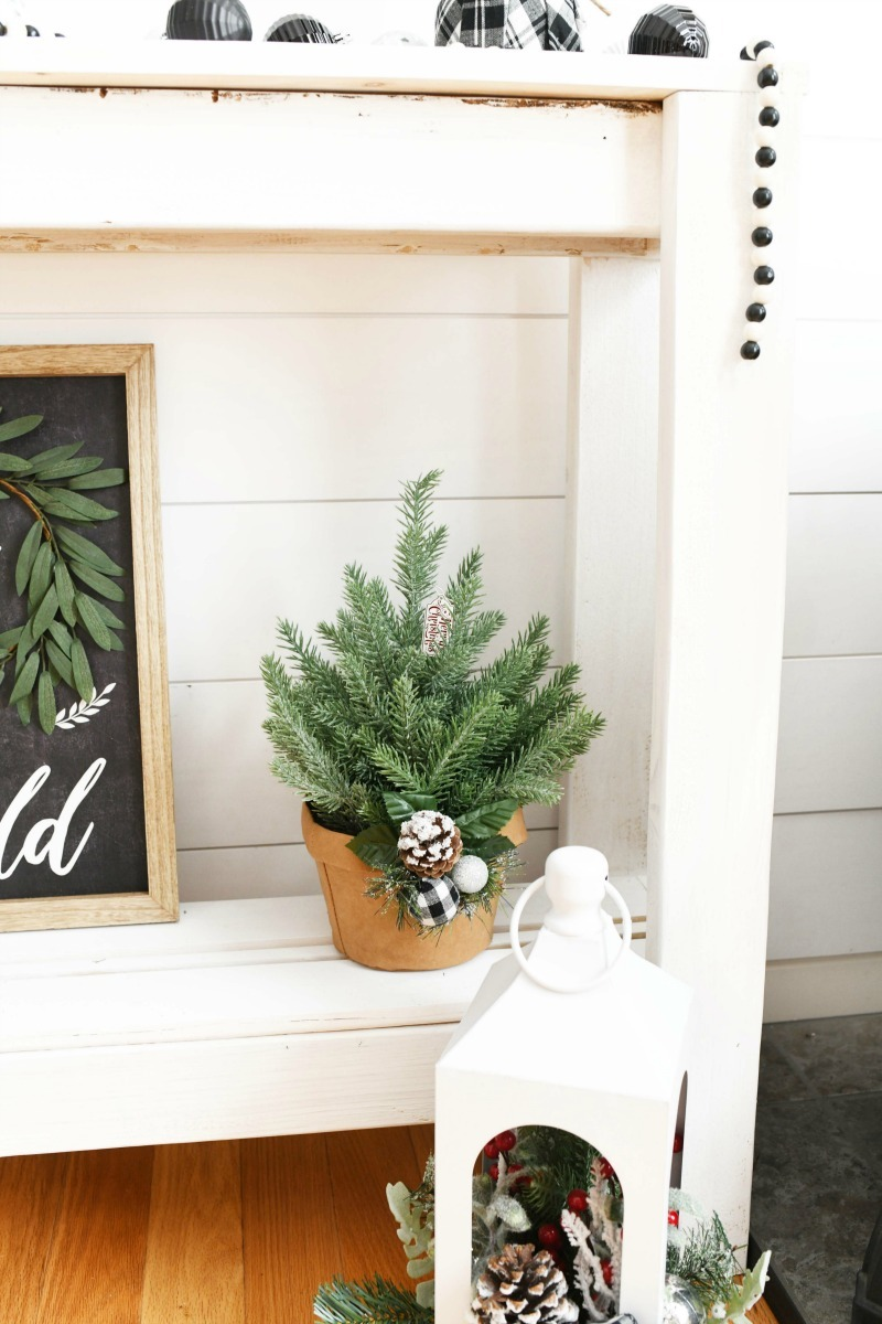 Faux potted pine plant on a white buffet table.