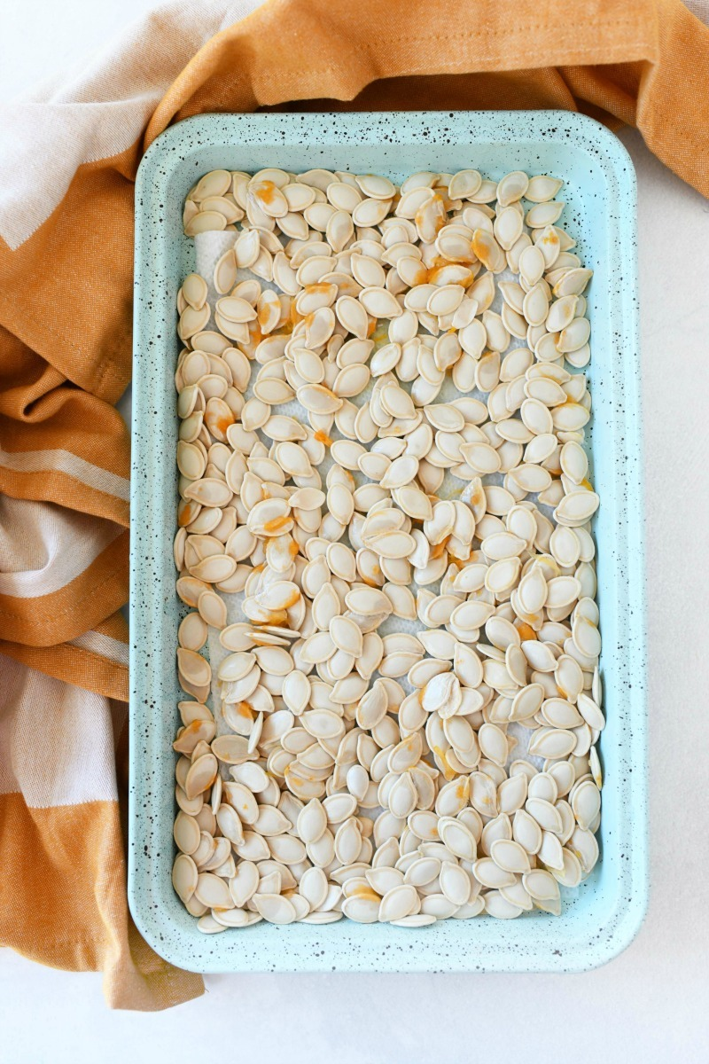Homemade pumpkin seeds air drying on a blue baking sheet.