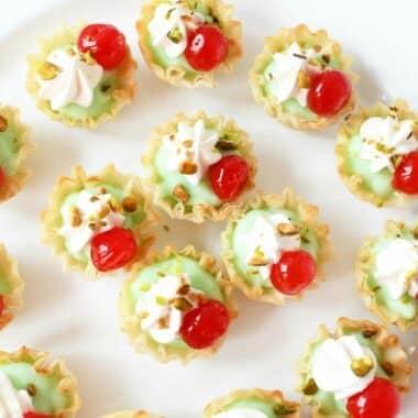 Pistachio Cherry 2-bite desserts on a white scalloped tray.