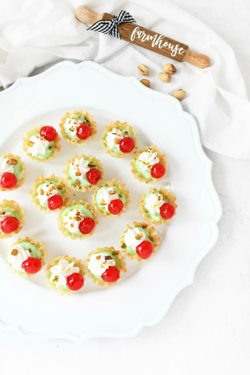Pudding bites with cherries on a white platter.