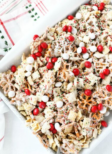 Buddy The Elf Chex Mix on a white parchment lined baking sheet with a white Christmas napkin.