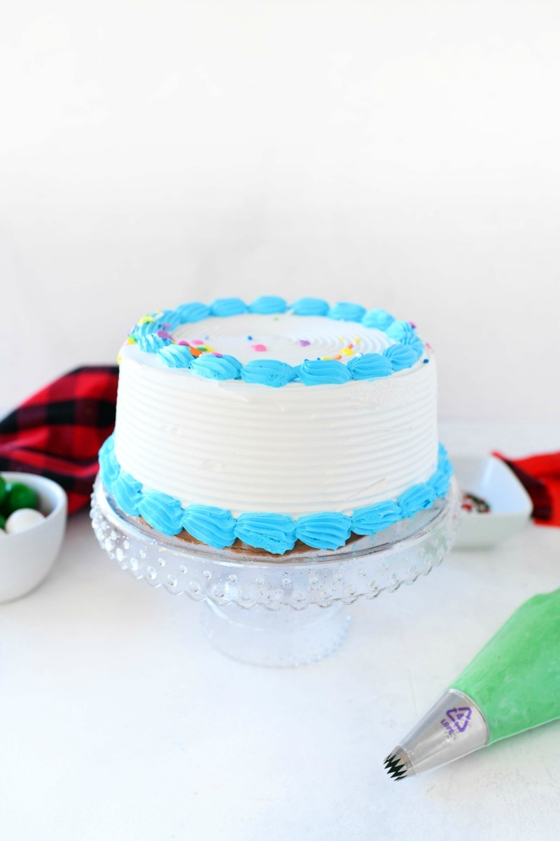 Carvel ice cream cake bare on a clear cake stand. There is a buffalo plaid napkin in the background with a green piping bag.
