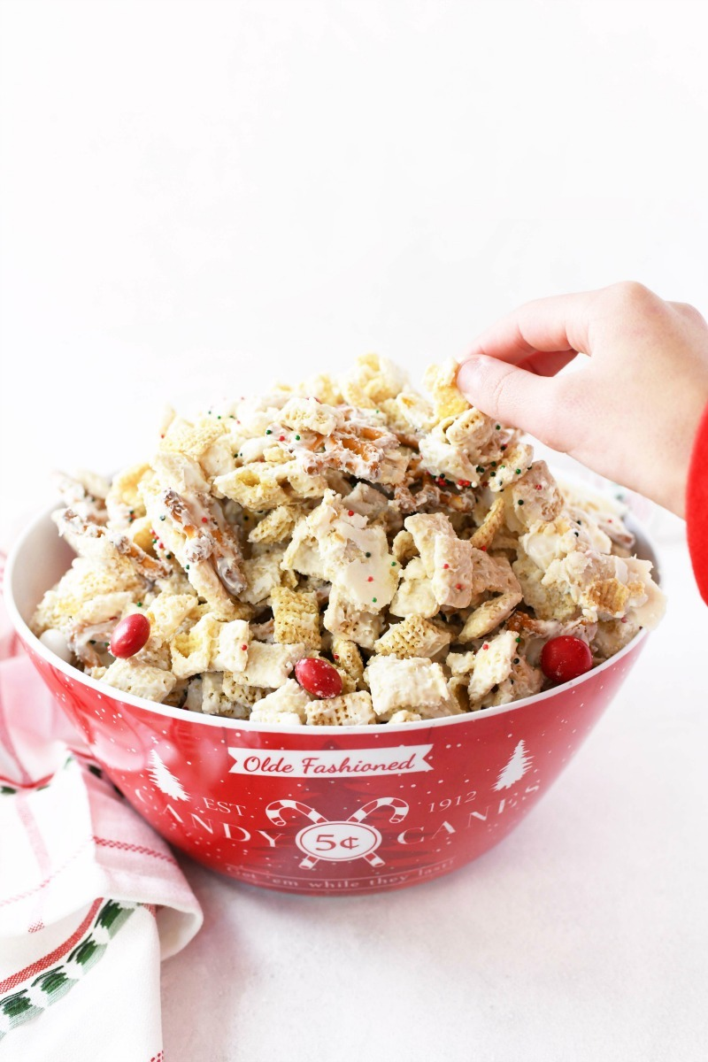Chex Christmas Mix in a red bowl with a kid's hand grabbing some. The kid is wearing a red shirt.