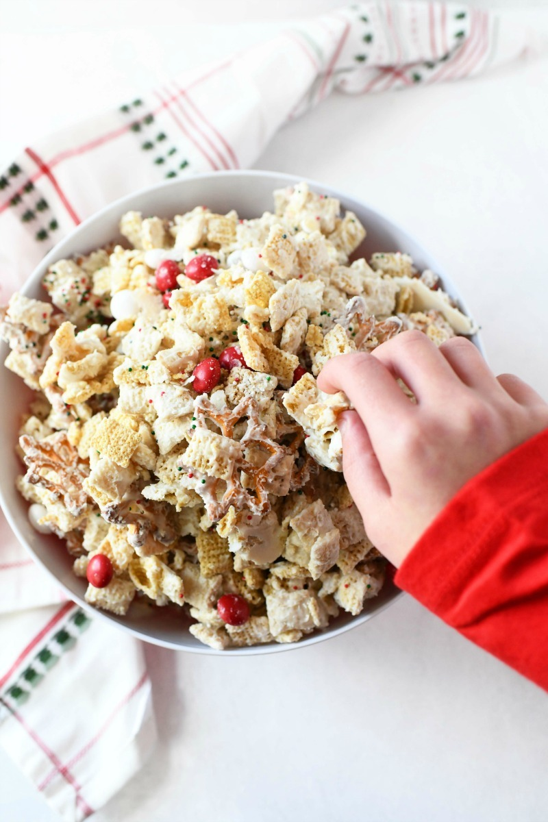 Chex Elf Mix ina  bowl with a kid's hand grabbing a piece. The kids is wearing a red shirt.