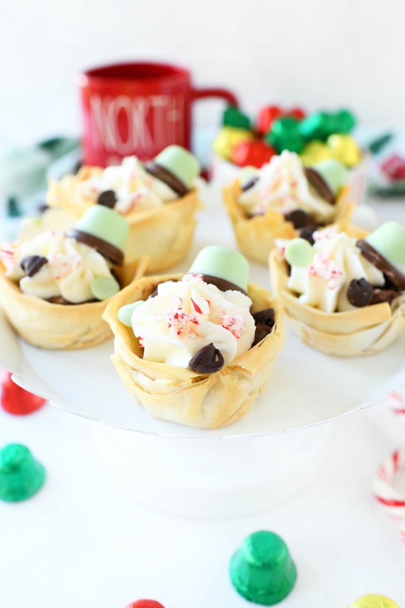 Chocolate Mint Cream Pies on a white stand with foiled bells nearby.