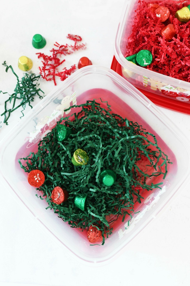 Plastic gift box filled with green shreds and minty bells.
