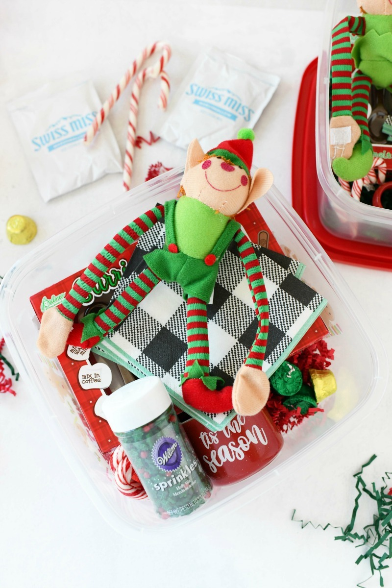 Christmas hot cocoa gift with an elf, plaid napkin, and holiday sprinkles.