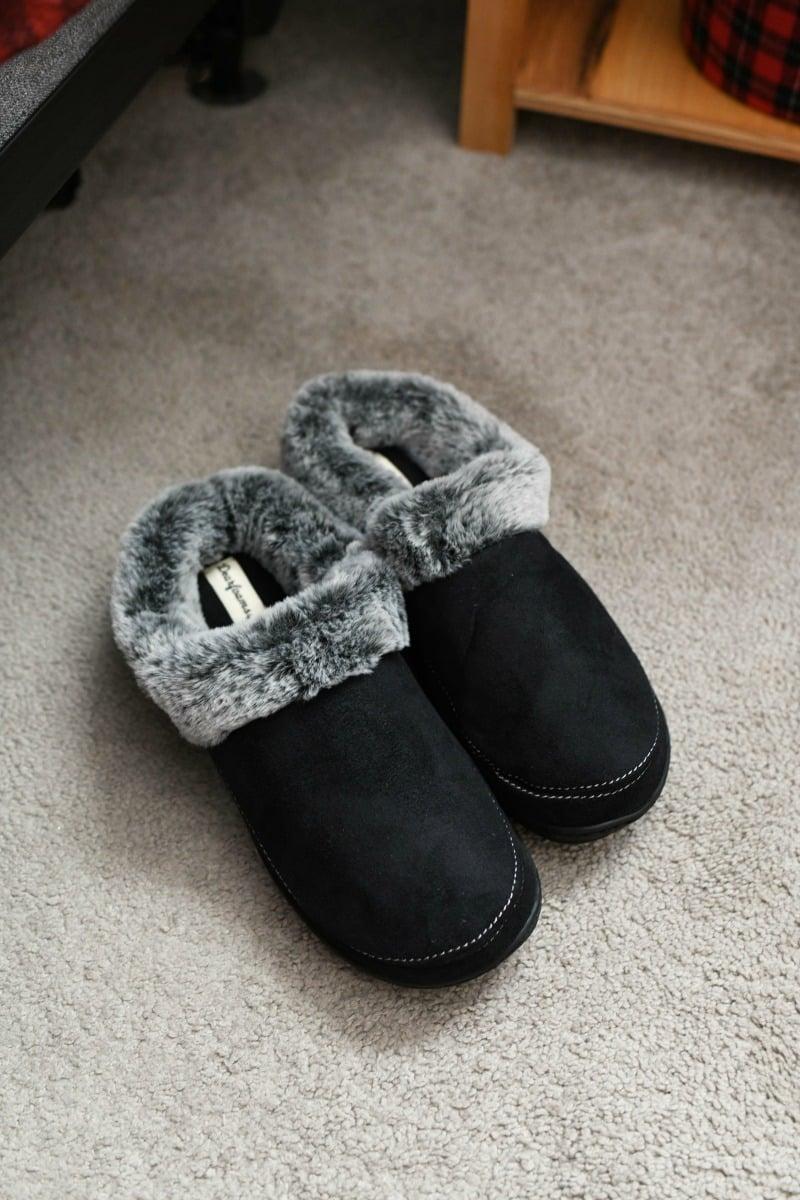 Dearfoam black slippers on a grey carpet.