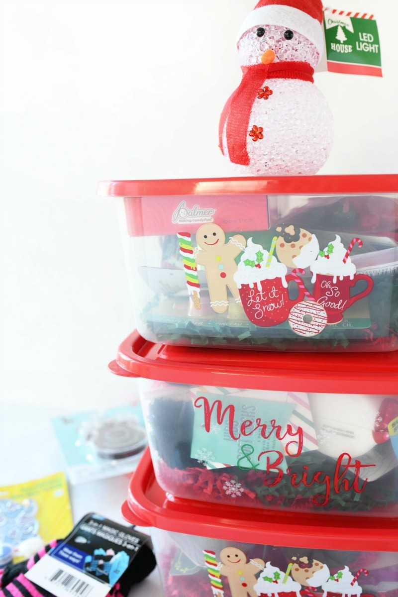 Dollar Store Gift Boxes stacked on each other. Boxes are red with holiday print and contain dollar store fillers.