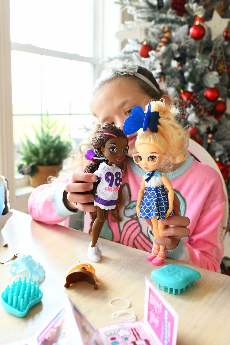 Girl playing with two Failfix dolls on a table.