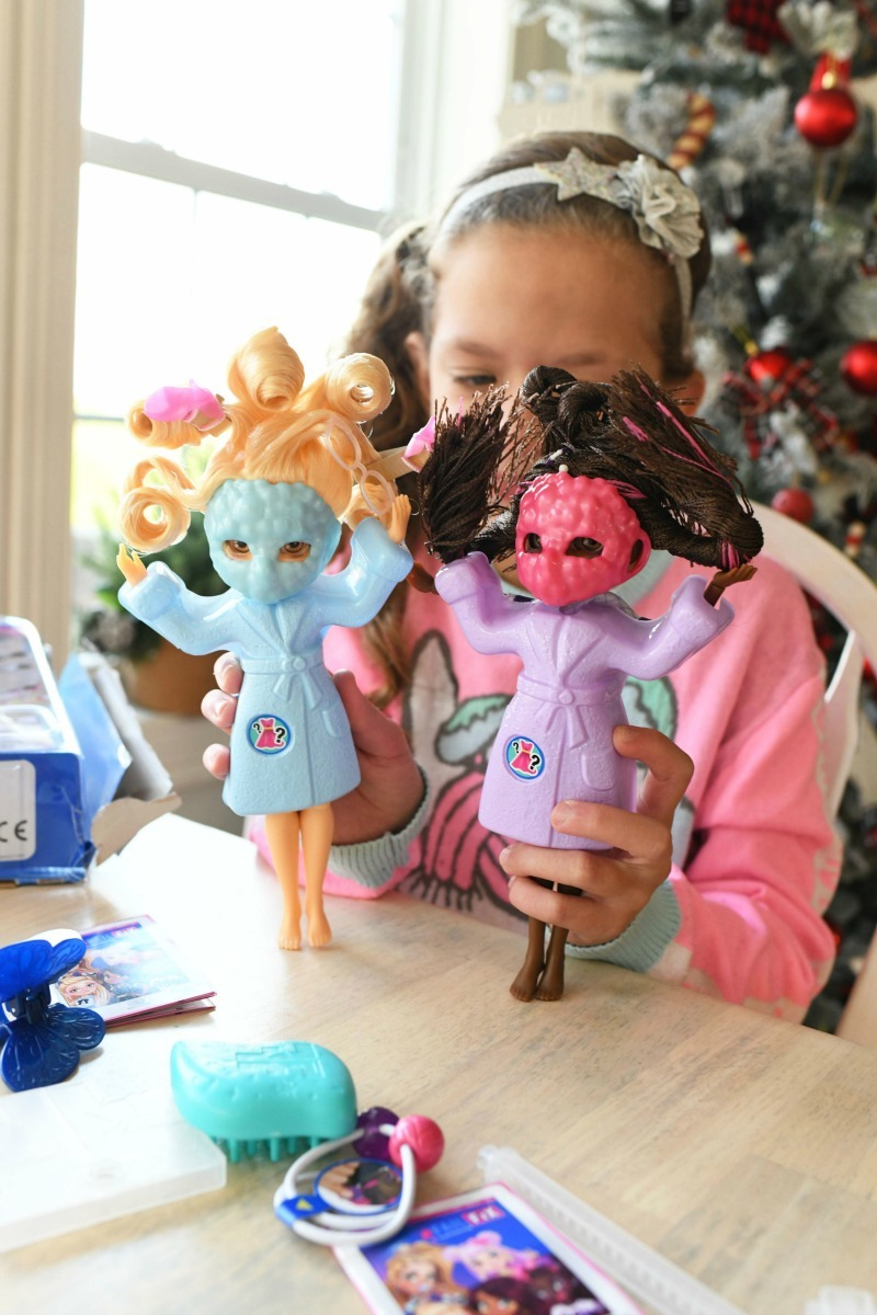 Girl holding two FailFix dolls with masks on.
