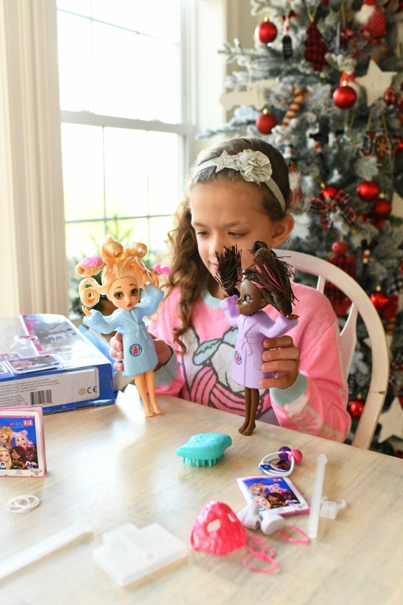 Little girl playing with FailFix fashion dolls. A christmas tree is in the background.