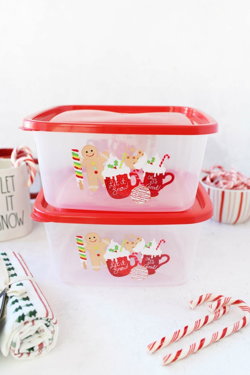 Gingerbread storage boxes with plastic and candy canes on a white table.