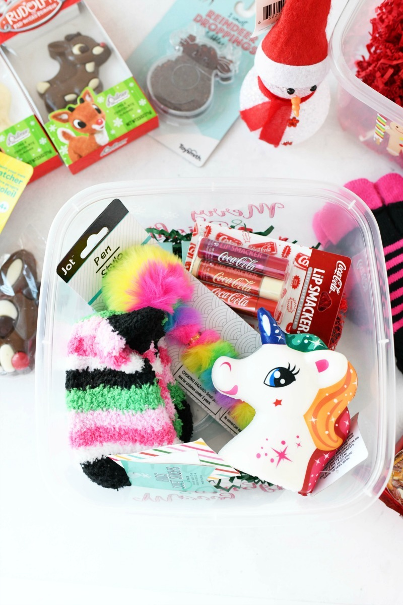 Girls dollar store gift box filled with brightly colored trinkets.