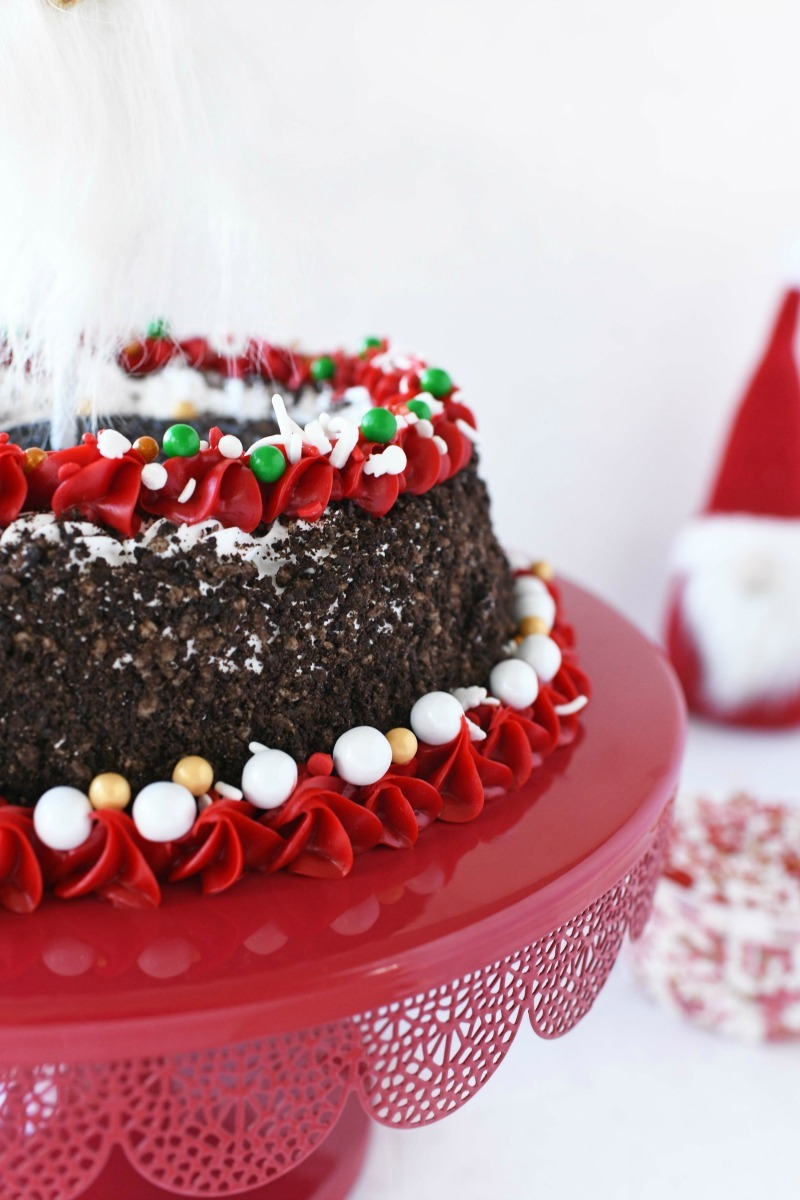 OREO ice cream cake decorated with red holiday frosting and sprinkles. It is sitting on a red cake stand.
