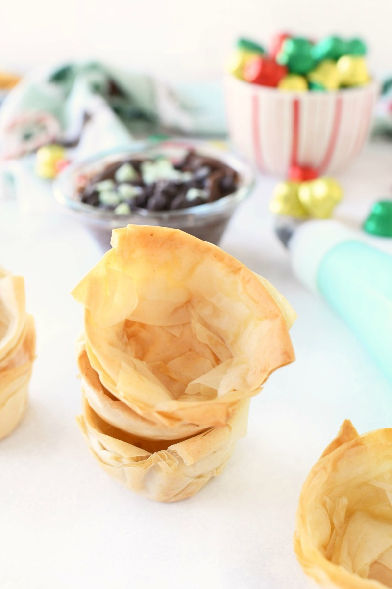 Golden phyllo dough baked cups stacked on a white table.