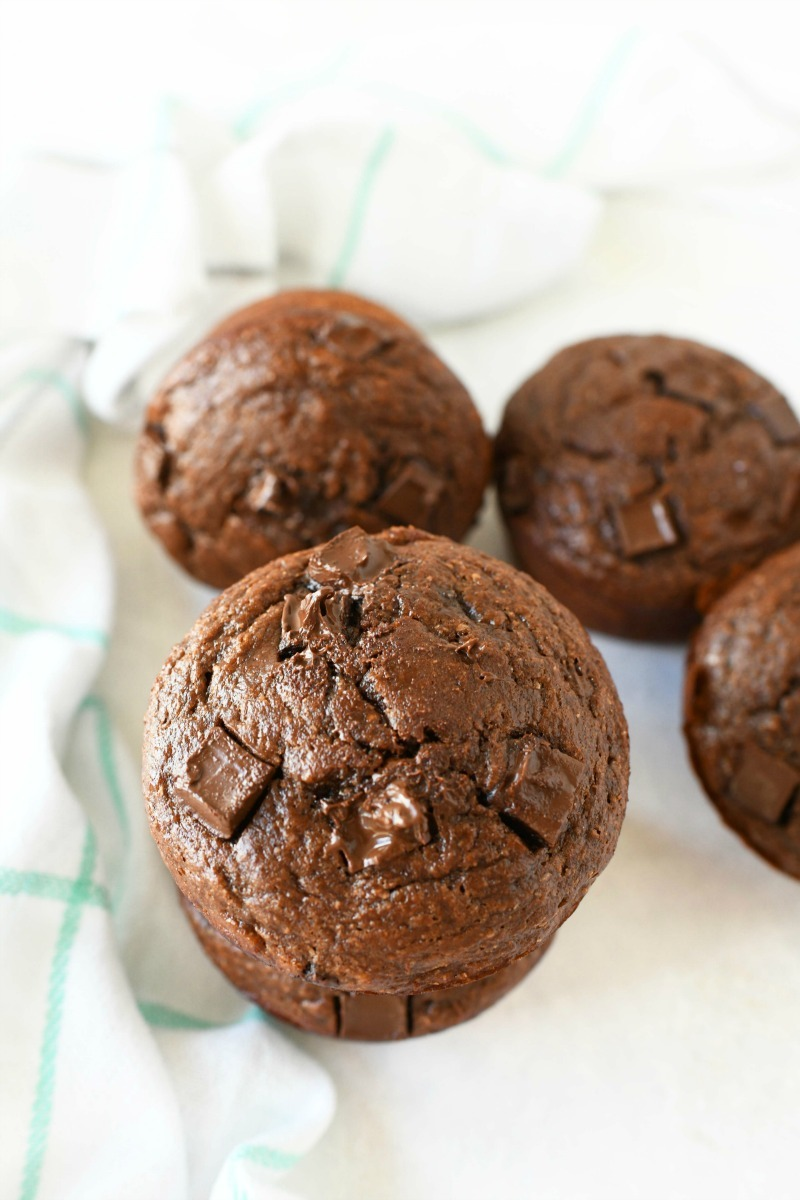 Healthy Chocolate Banana muffins on a white table with a checkered napkin.