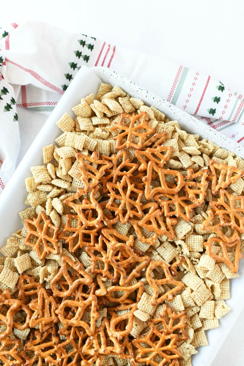 Holiday Chex Mix on a white parchment-lined baking sheet with a Christmas napkin.