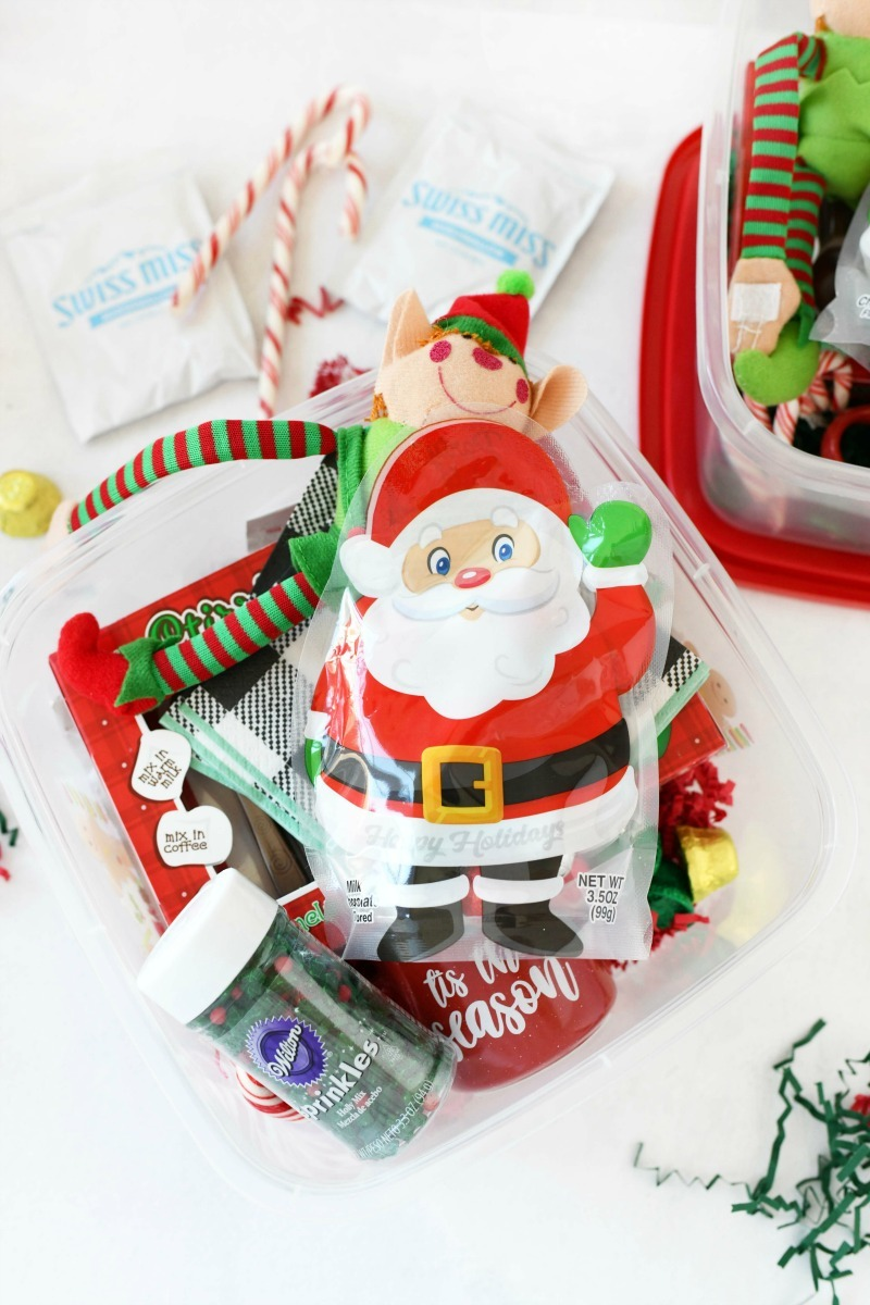 Hot Cocoa Gift set filled with holiday candy & trinkets on a white table.