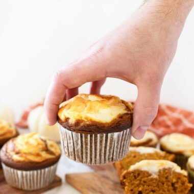 Man putting a pumpkin cream cheese muffin on a table near other muffins.