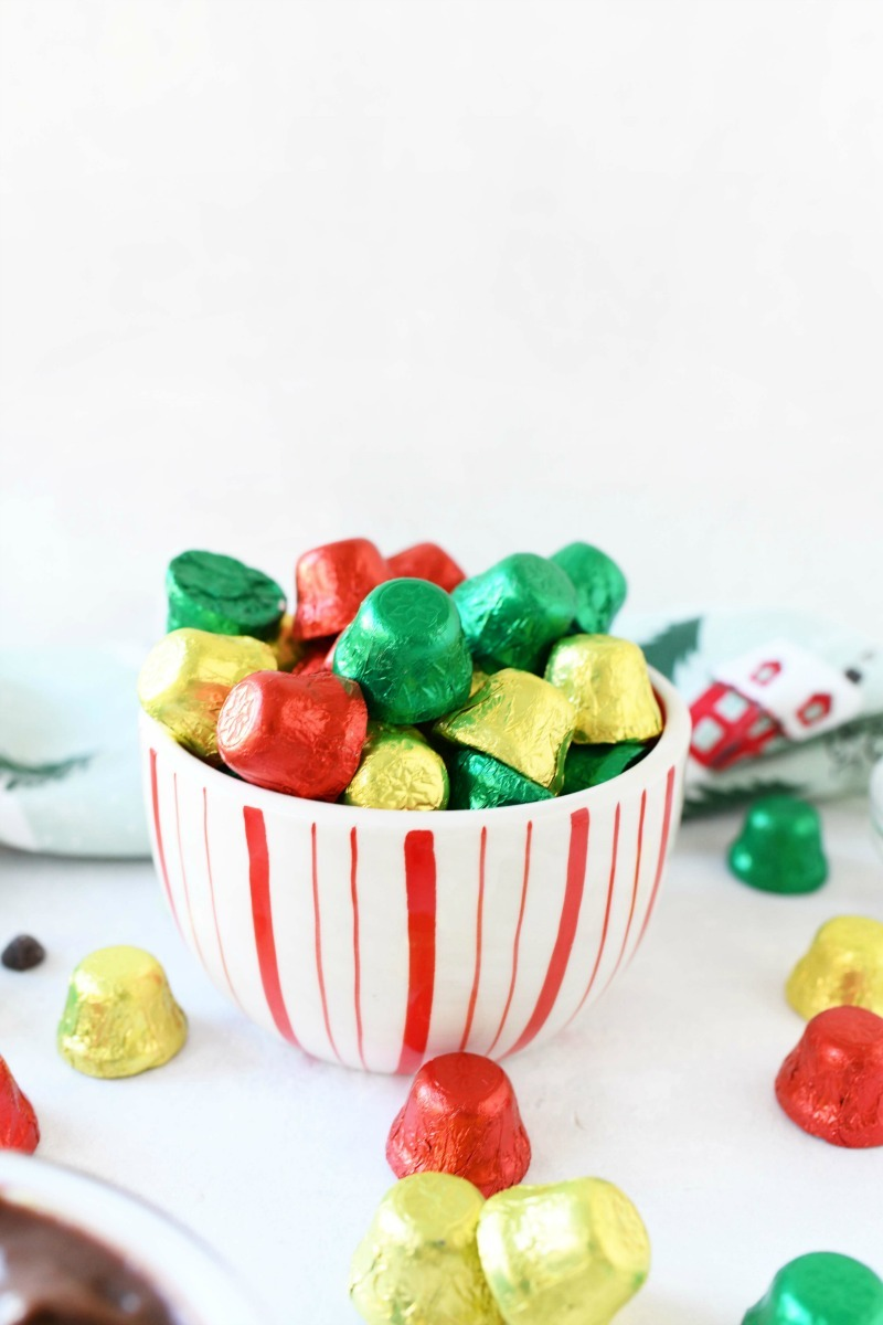 Minty Bells Palmer Chocolate in a peppermint designed bowl. Foiled bells are strewn around the table.