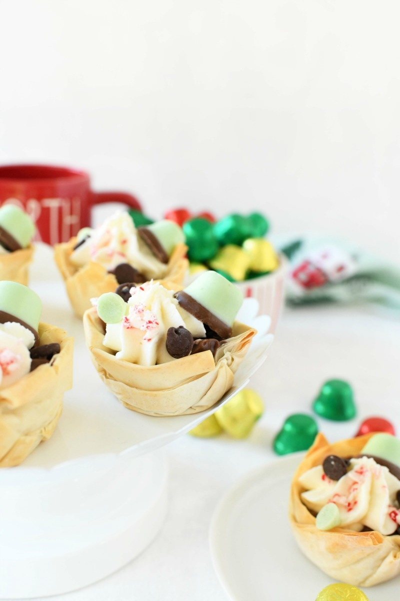 Phyllo dough desserts with chocolate pudding, candies, and cream on a white table.