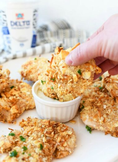 Ritz Cracker Crusted Chicken cutlets being dipped in ranch.