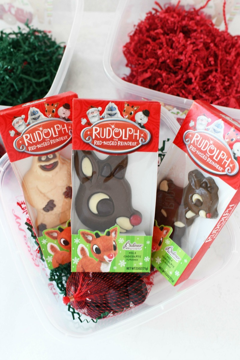 Rudolph Chocolate Candy on a white table near red and green filled boxes.