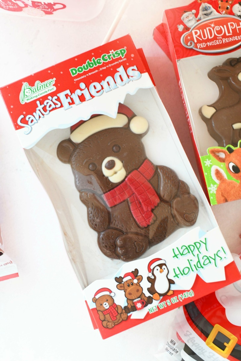 Santa's Friend bear chocolate on a white table. Bear has a red scarf and white hat.