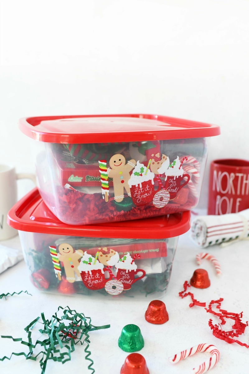 Ten dollar Christmas Cocoa Gift- two red lidded gift boxes stacked with candies and green shreds on a white table.
