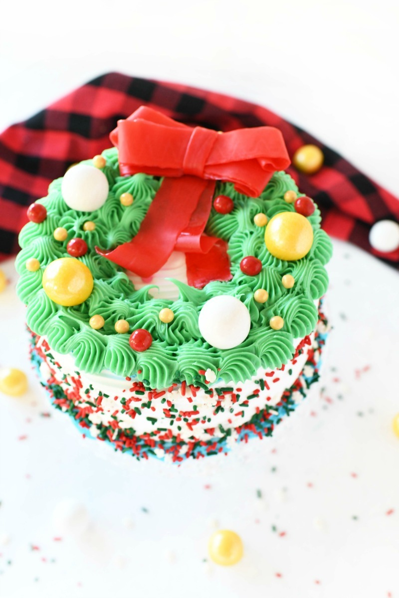 Carvel Wreath Cake with a red fruit by the foot bow on top.