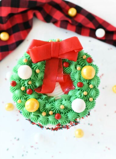 Wreath Carvel Ice Cream Cake on a white table with candies spilled around. There is a buffalo plaid napkin on the table near the cake.
