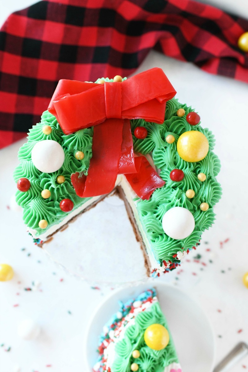 Wreath Ice Cream cake sliced with a slice on a small white plate. A red plaid napkin is in the background.