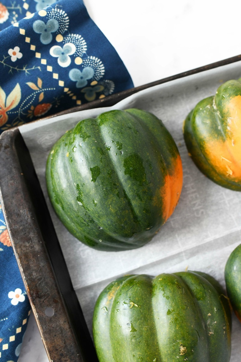 Baked Acorn Squash on a parchment-lined baking sheet with a blue flowered napkin.