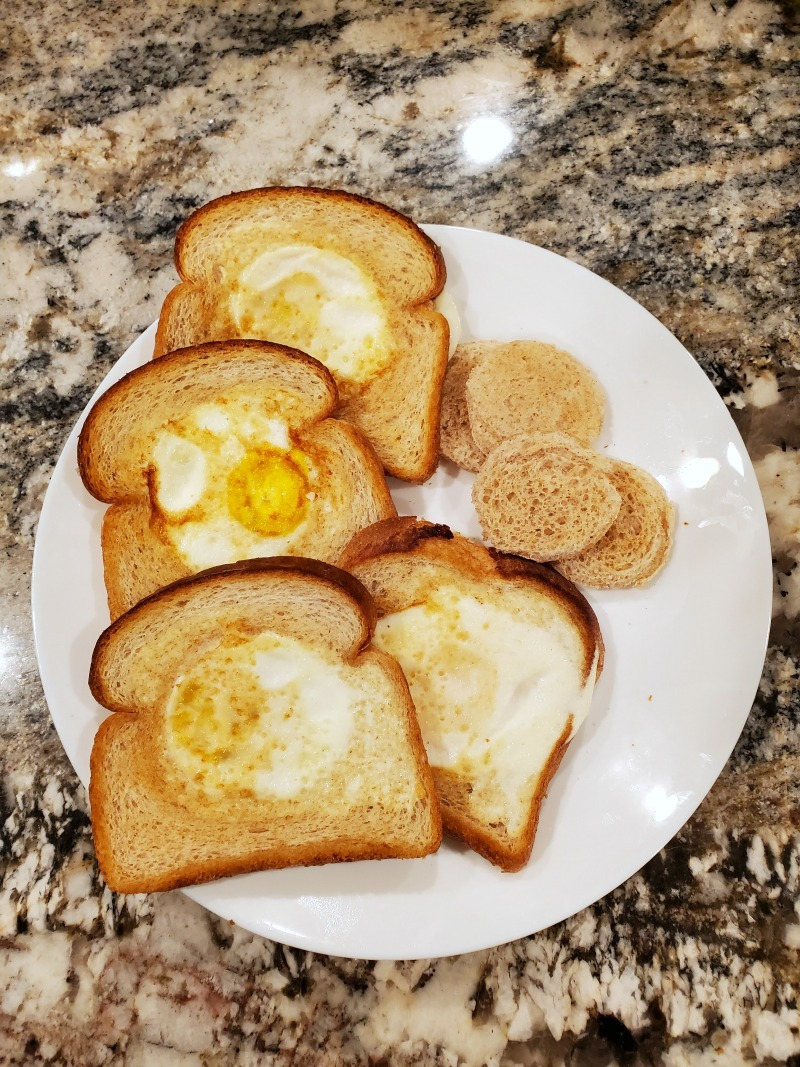 Birds Nest Egg bread on a white plate sitting on a granite countertop