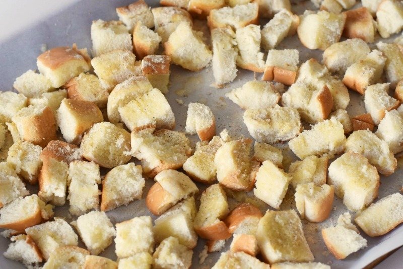 Homemade Bread Croutons unbaked on a parchment lined baking sheet.