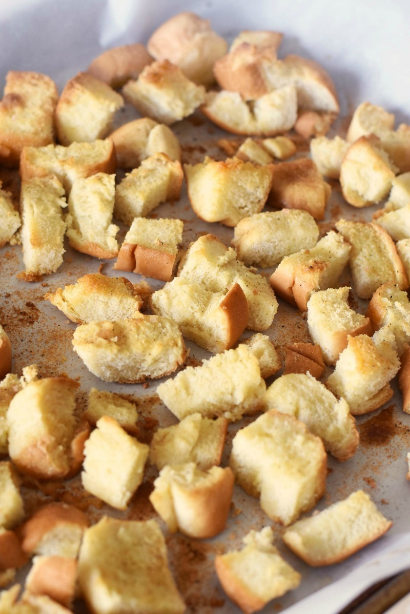 Homemade Croutons toasted on a parchment lined baking sheet.