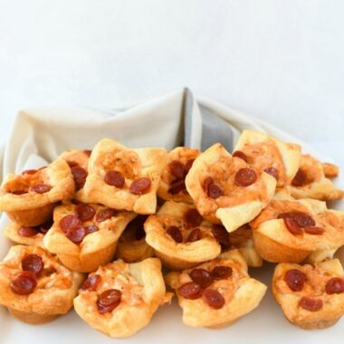 Pepperoni Pizza Crescent Dough Dip Bites with a grey and white striped napkin on a white plater, stacked.