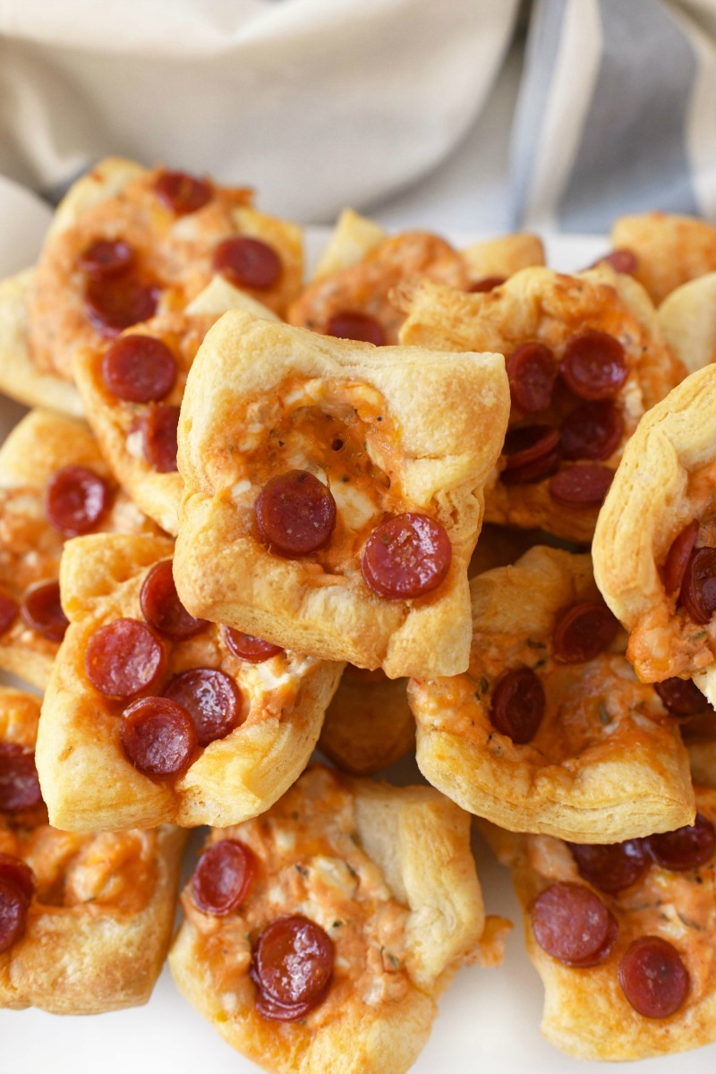 Pepperoni Pizza Dip Bites are stacked on top of each other and baked until a golden brown perfection.