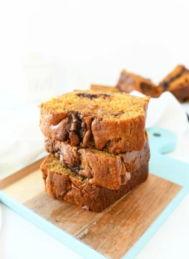 Pumpkin Chocolate Bread sliced on a blue and wooden cutting board.