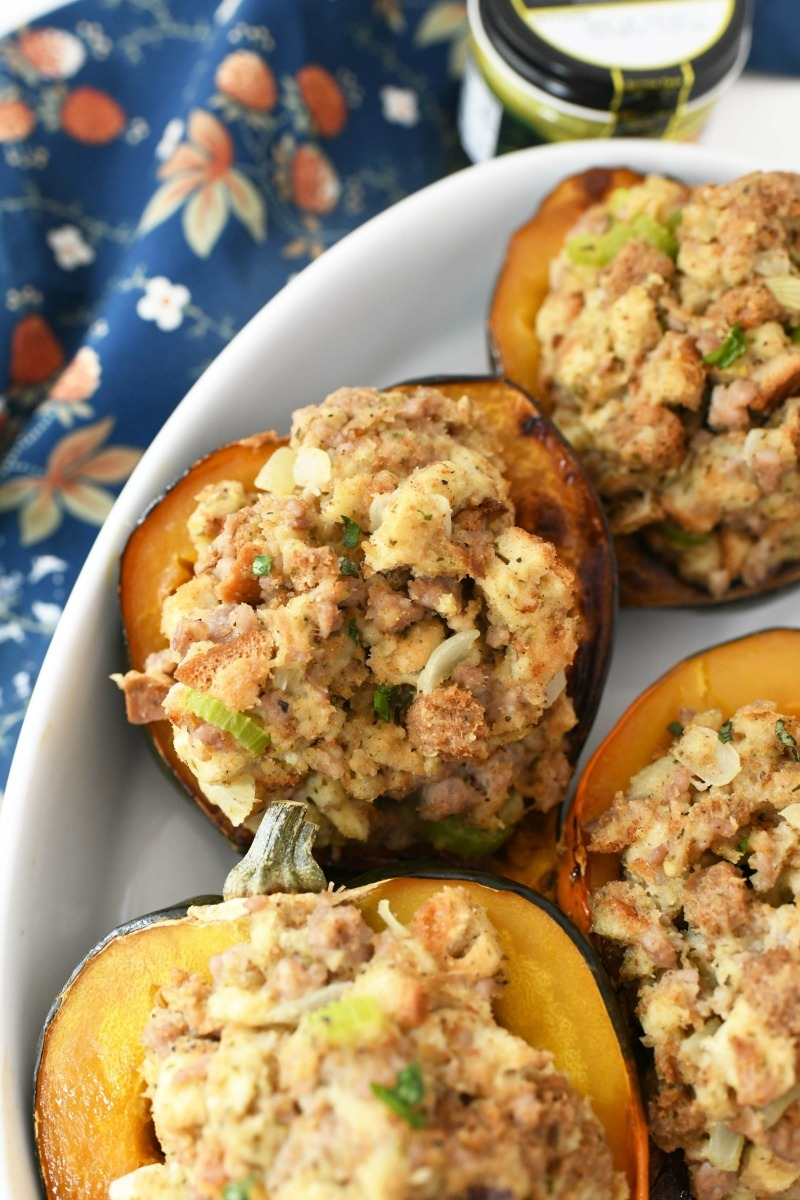 Sausage Stuffed Acorn Squash in a pan with a blue floral napkin