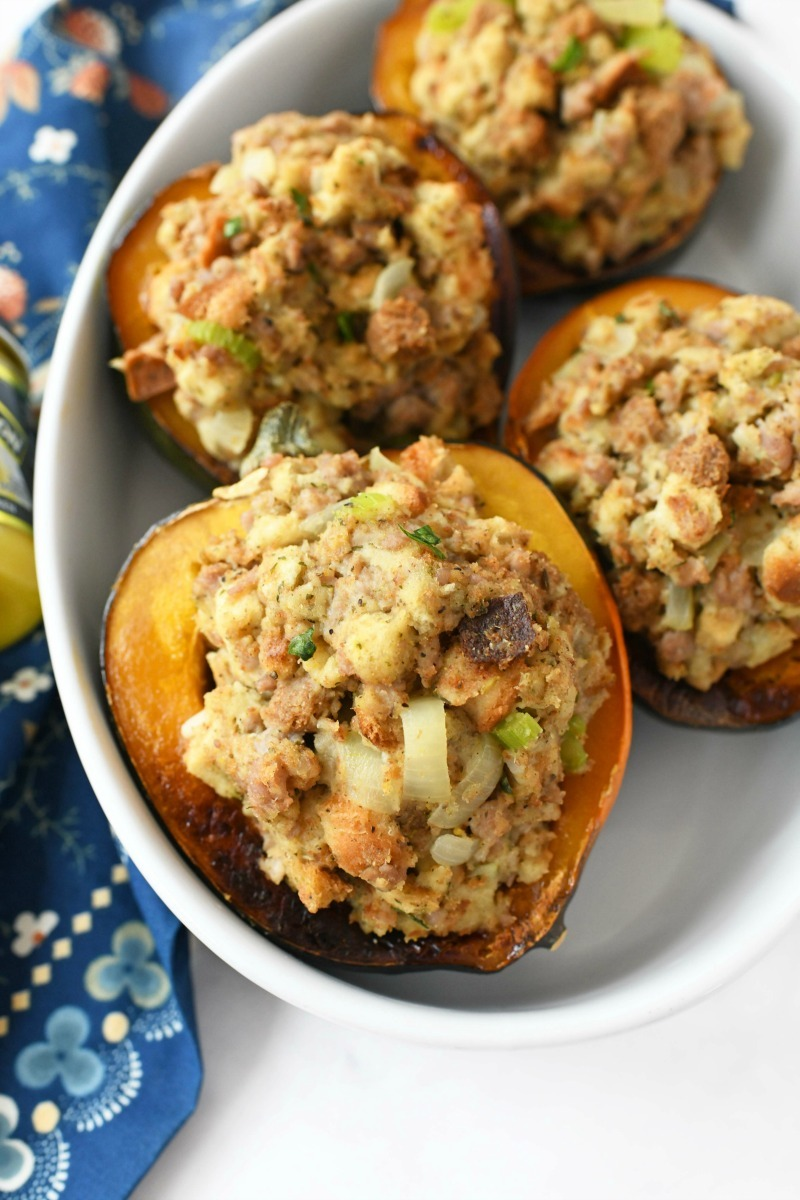 Sausage Stuffed Baked Acorn Squash in a white oval baker with a blue, floral napkin.