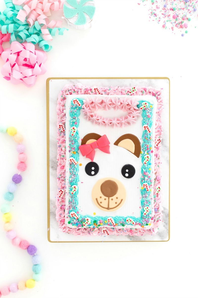Ugly sweater cake is pink and blue with a teddy face on it. It is on a white table with pastel decor.