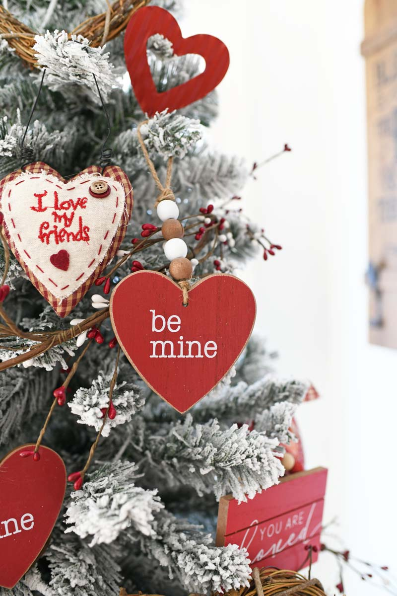 Be Mine Wooden Heart Ornament on a flocked tree with red and cream colored ornements.