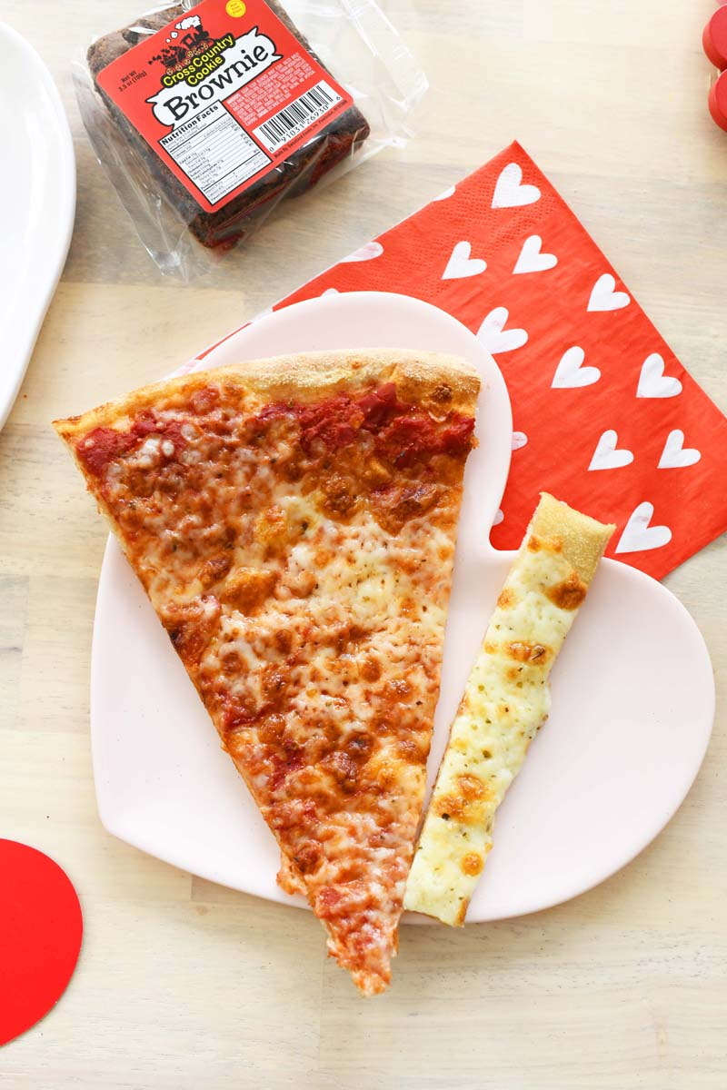 Cheese pizza on a heart plate. There is a red heart napkin also on the table.