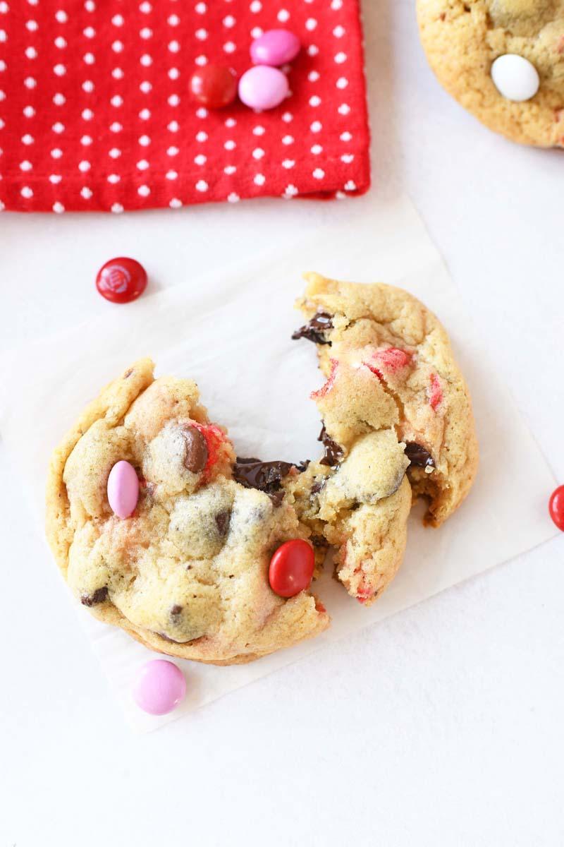 Chewy Melty Chocolate Chip Cookie with Valentine colored M&Ms. The cookie is warm and melty. There is also a red dot napkin and pink M&Ms on the white table.