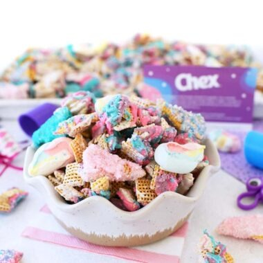 Colorful Unicorn Chex Snack Mix in a Bowl with small pieces of the mix on a white table.