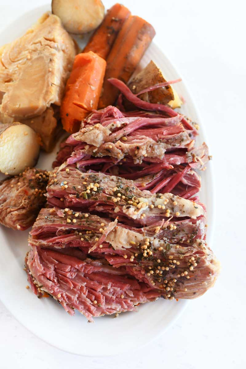 Sliced, seasoned corned beef with carrots, potatoes, and cabbage.